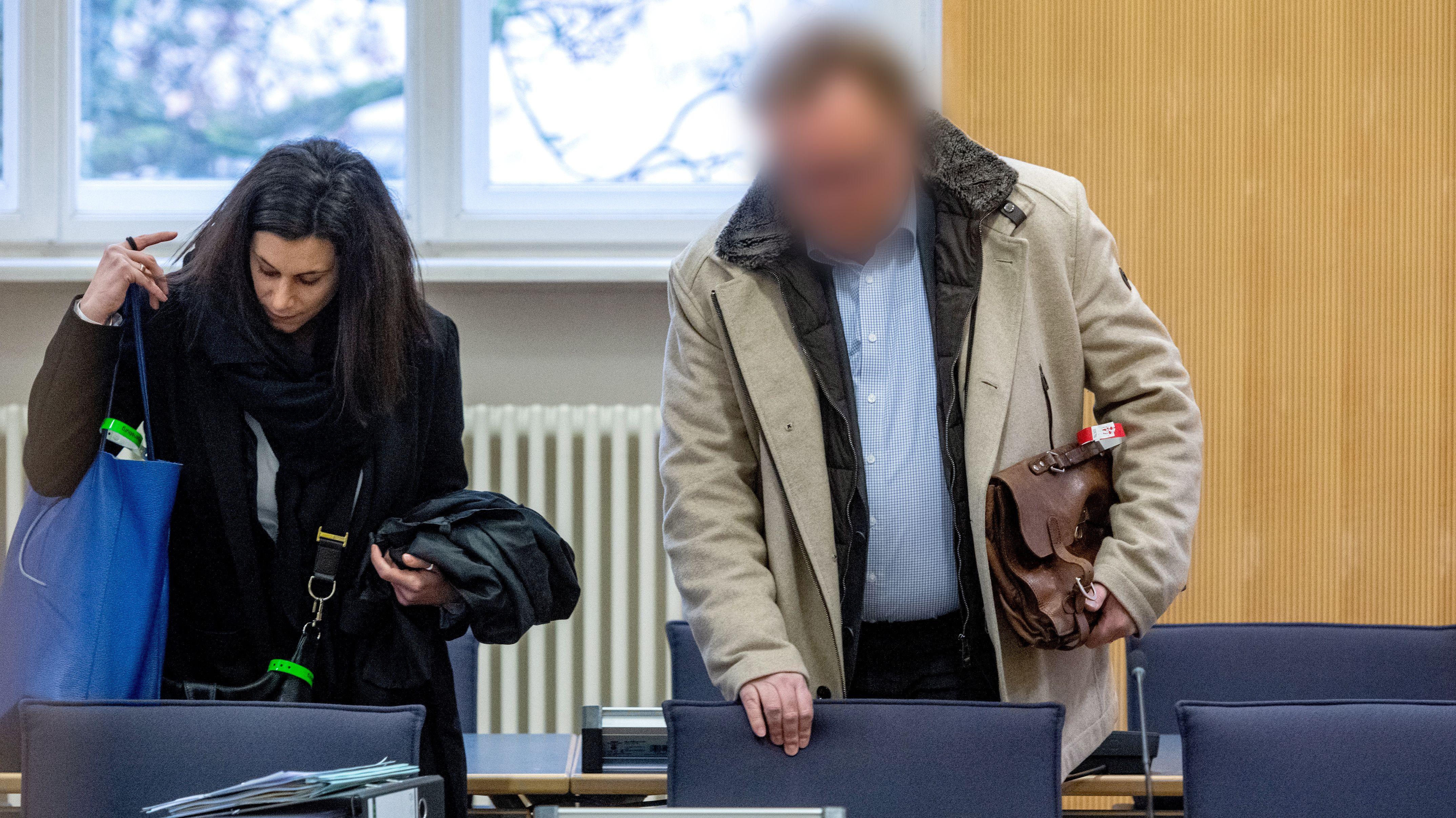 Der Angeklagte steht im Verhandlungssaal des Landgerichts neben seiner Verteidigerin Daniela Gabler.