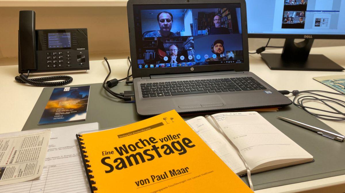 Vor einem Laptop mit Videokonferenz liegt eint Textbuch zu den Kreuzgangspielen