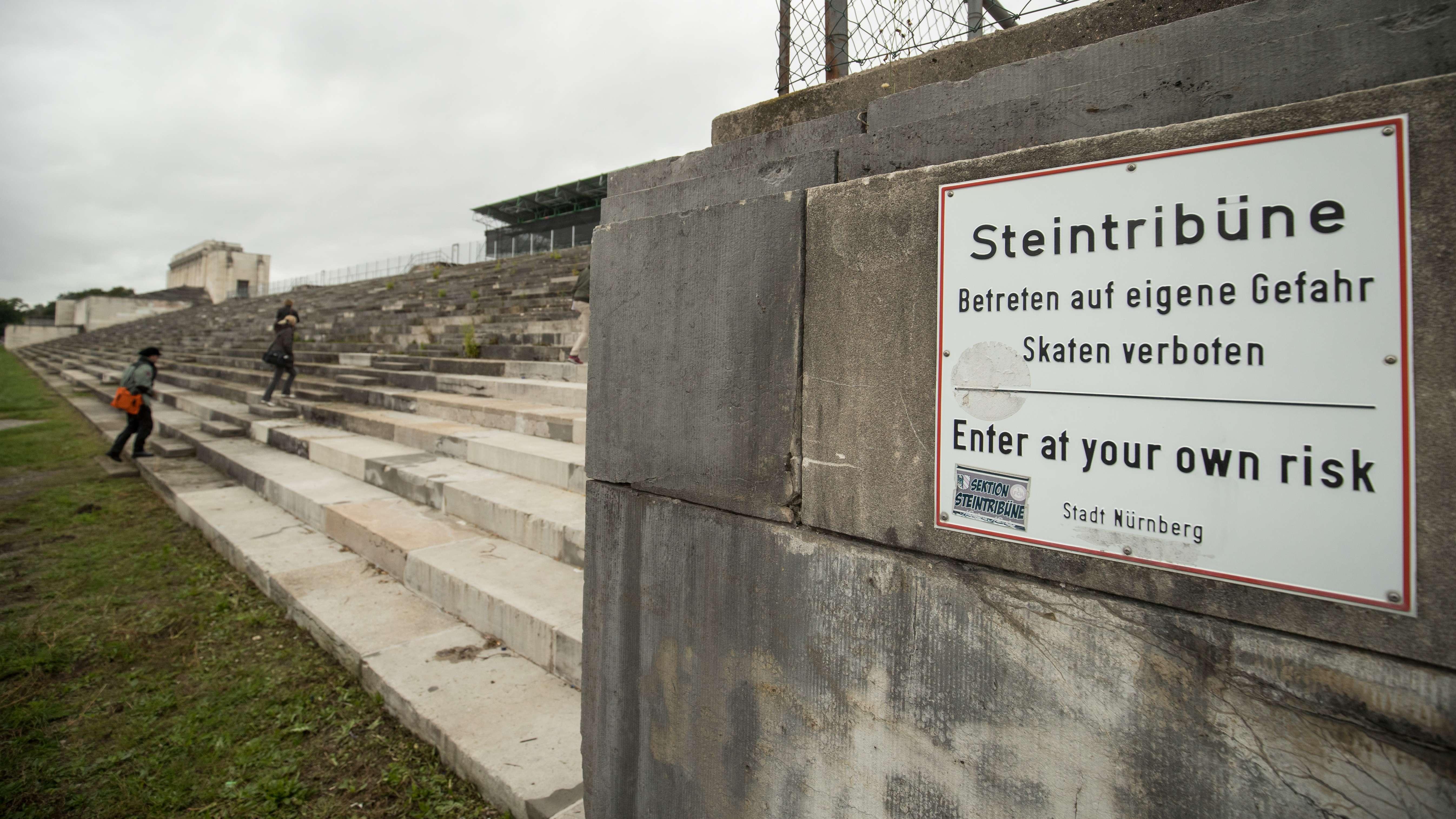 """Schild mit der Aufschrift """"Steintribüne - Betreten auf eigene Gefahr"""" an den Stufen der Zeppelintribüne auf dem ehemaligen Reichsparteitagsgelände in Nürnberg"""