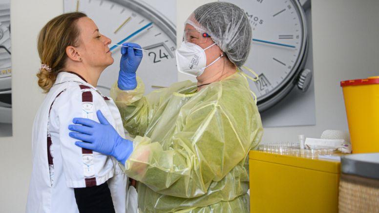 Ein Corona-Test in einer deutschen Uhrenmanufaktur. Eine Angestellte in Schutzausrüstung führt einen Corona-Test an einer Kollegin durch.