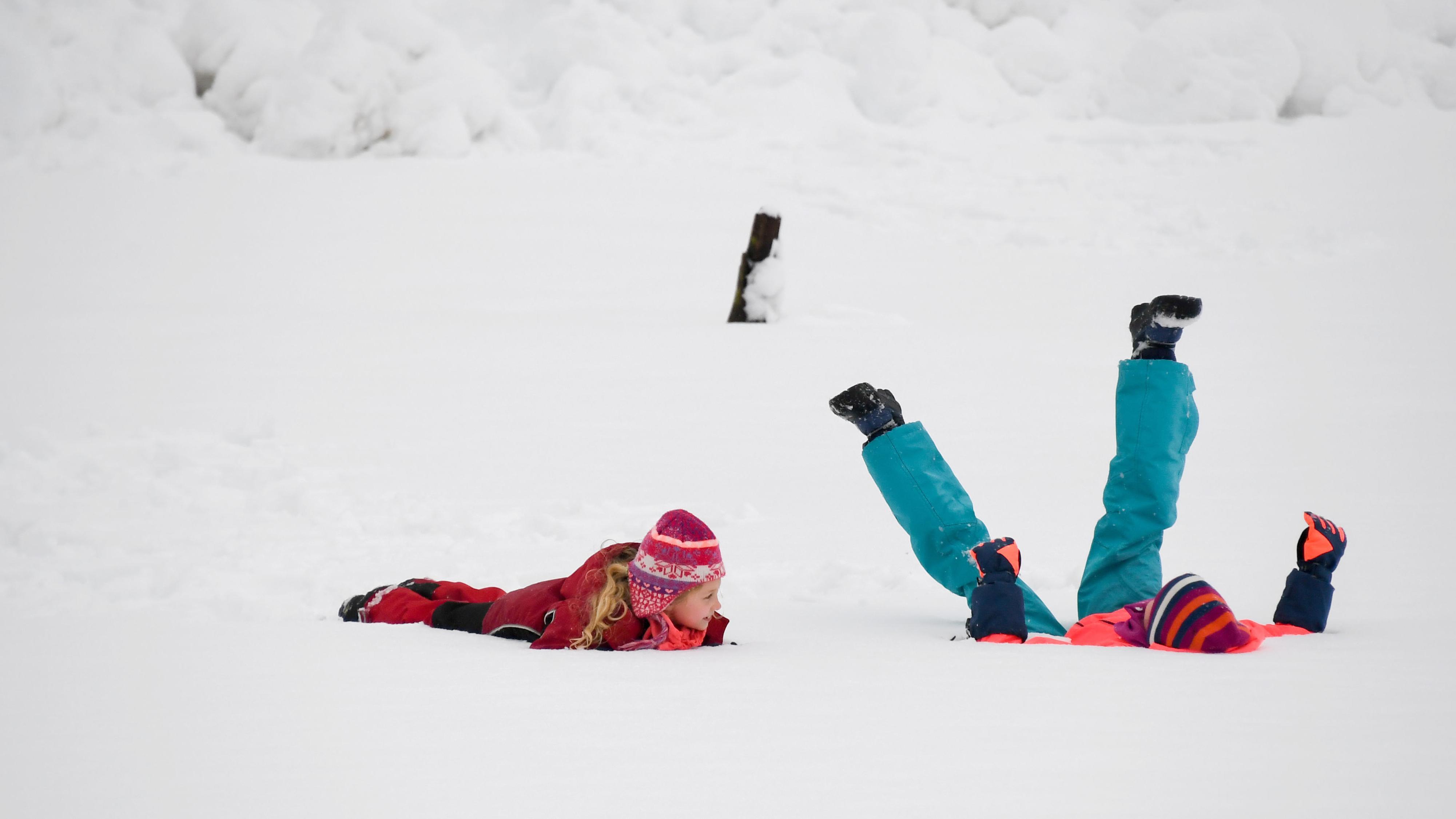 Traunstein: Zwei 8- und 10-jährige Mädchen in bunter Winterkleidung liegen im Schnee