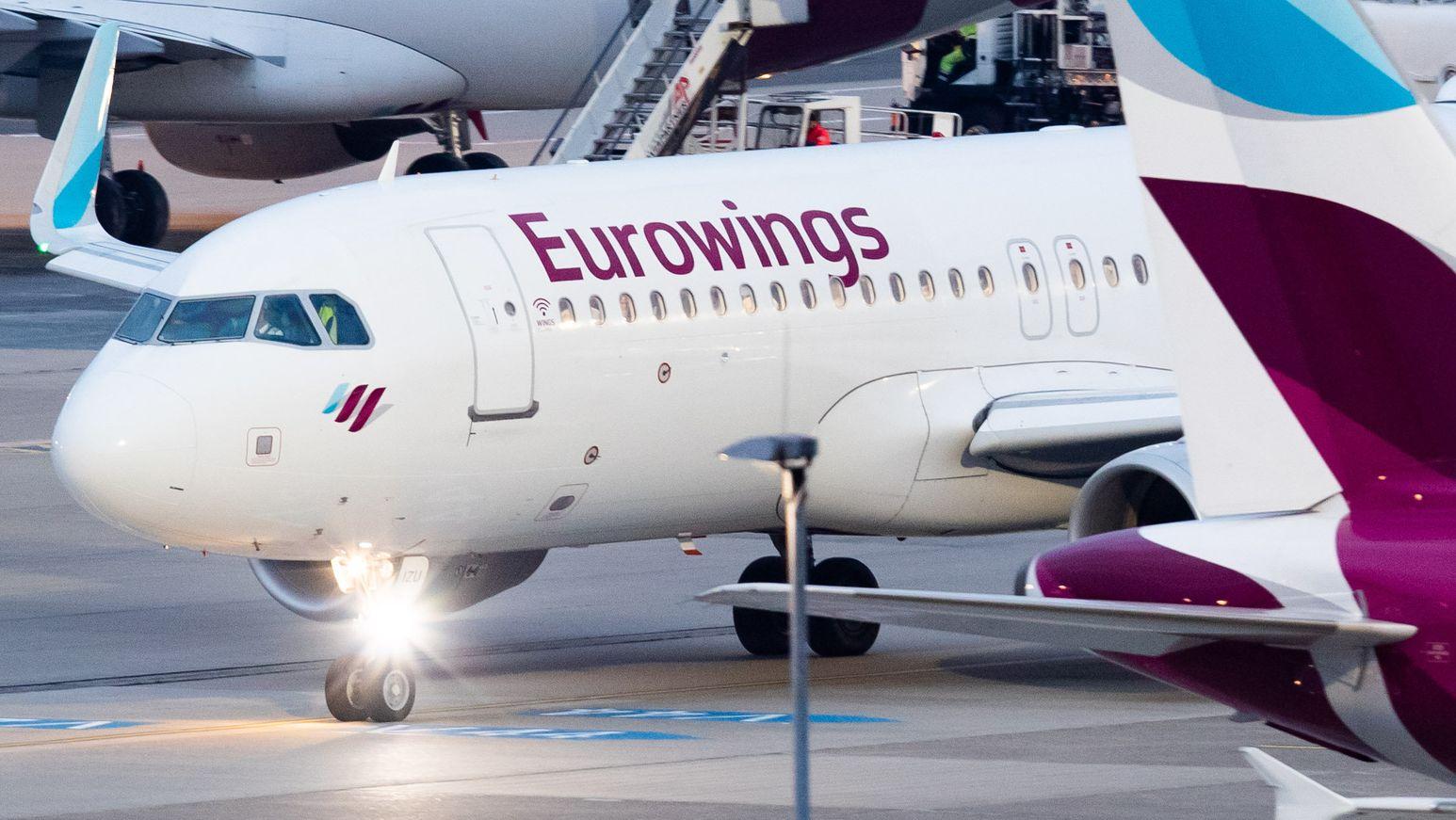 Ein Flugzeug der Fluggesellschaft Eurowings rollt am Düsseldorfer Flughafen über das Vorfeld an parkenden Flugzeugen vorbei.