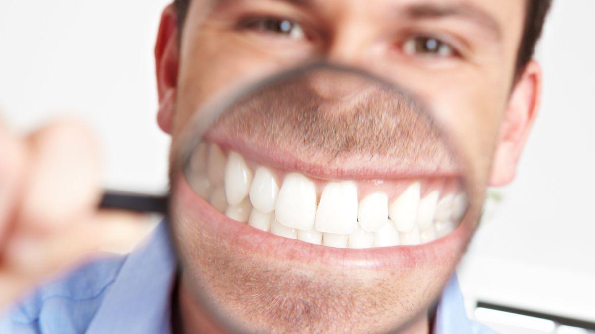 Grinsender Mann im Büro mit einer Lupe vor dem Mund.