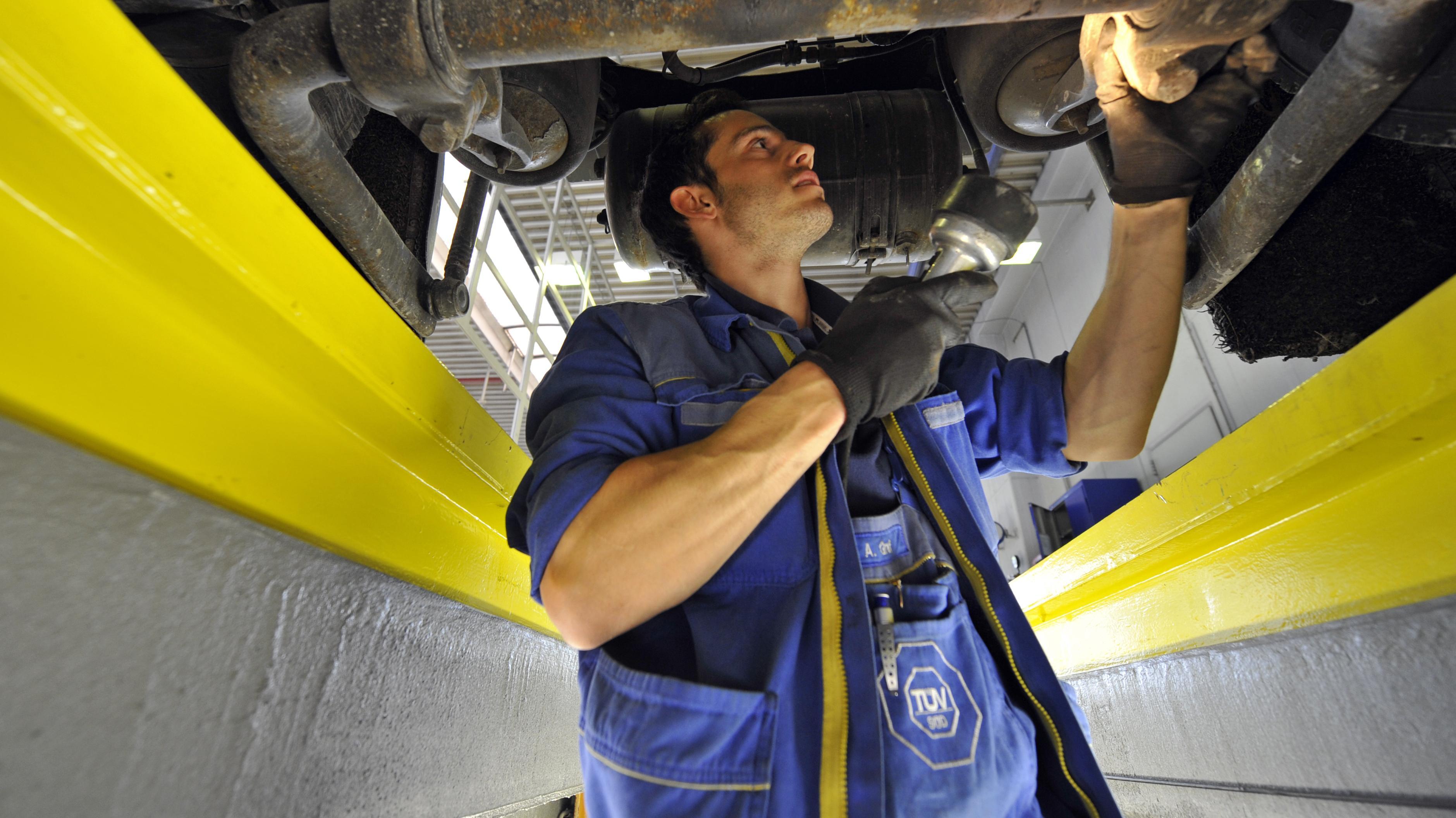 Ein TÜV-Mitarbeiter im Blaumann untersucht den Unterboden eines Autos (Symbolbild).