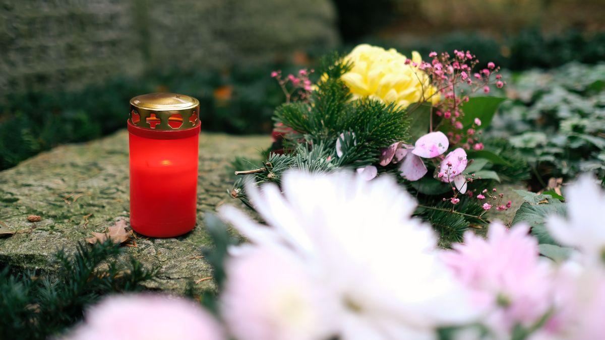 Grablicht auf einem Friedhof, daneben liegen Blumen.