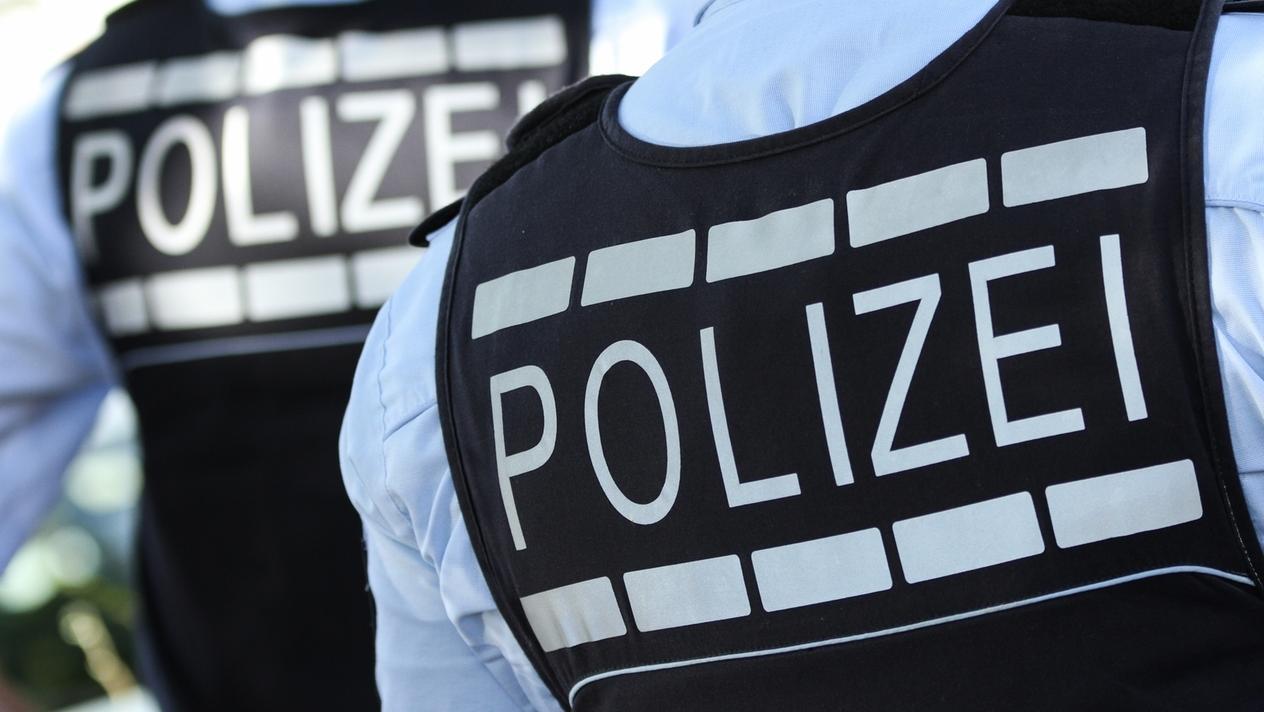 """Zwei Personen, die Westen tragen, auf denen """"Polizei"""" steht"""
