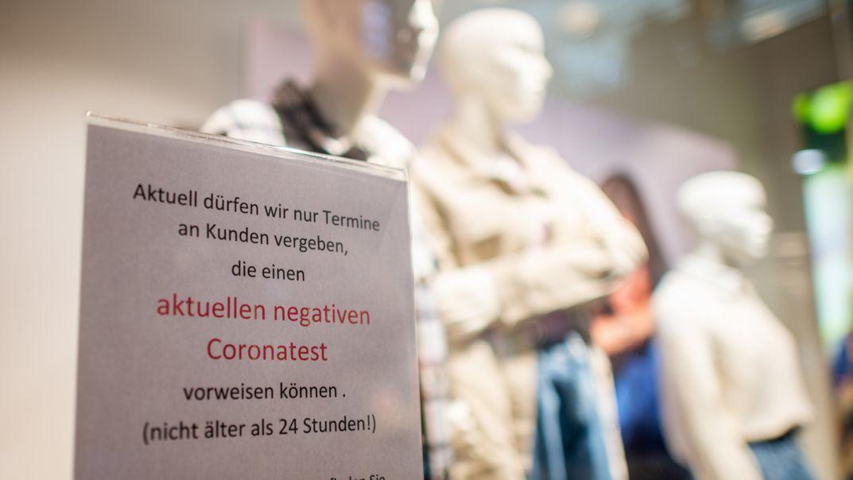 Ein Schild mit der Aufschrift ·Aktuell dürfen wir nur Termine an Kunden vergeben, die einen aktuellen negativen Coronatest vorweisen können· hängt in einem Geschäft