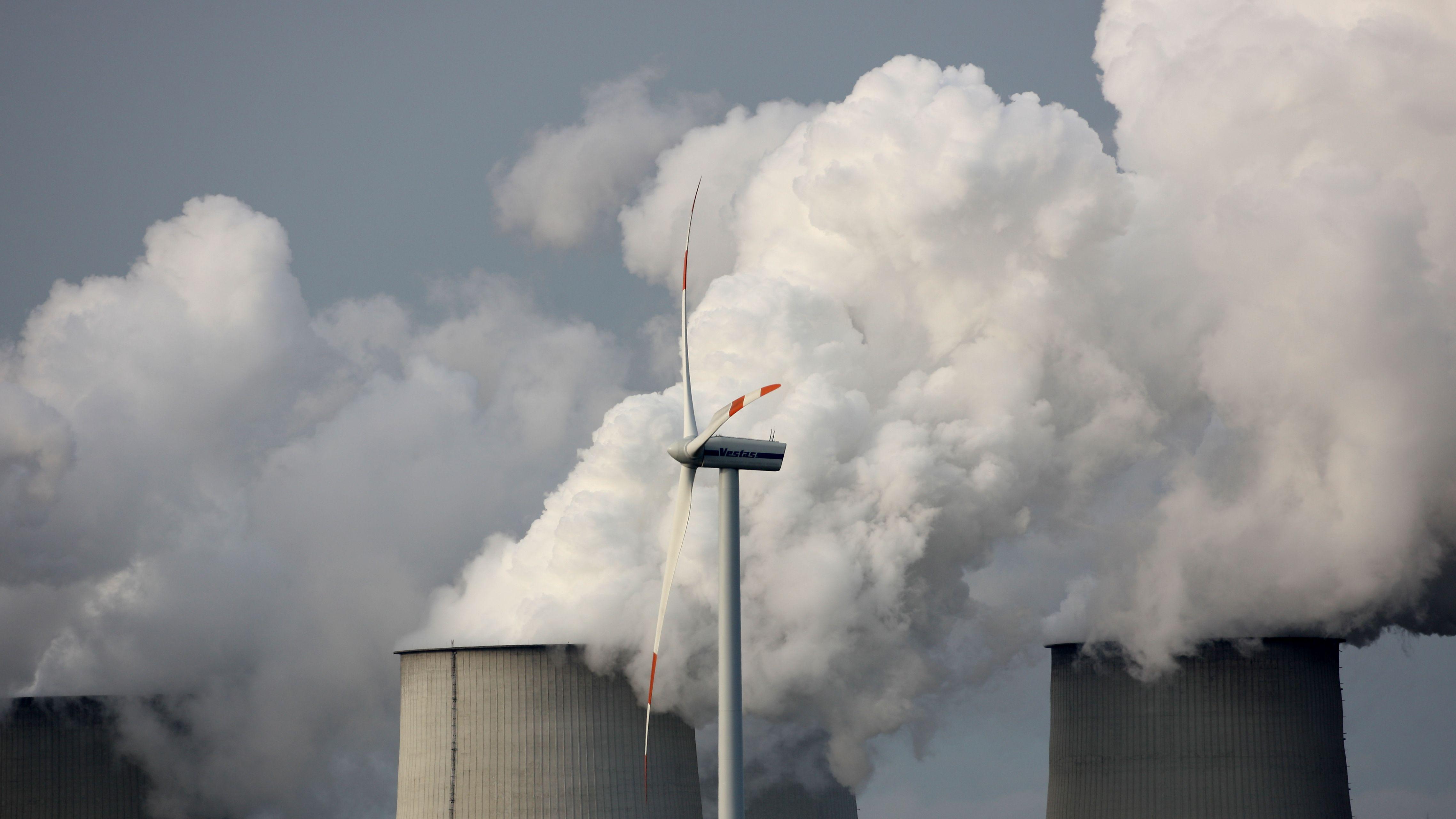Ein Windrad dreht sich unweit des Vattelfall Braunkohlekraftwerkes im brandenburgischen Jänschwalde vor den Kühltürmen