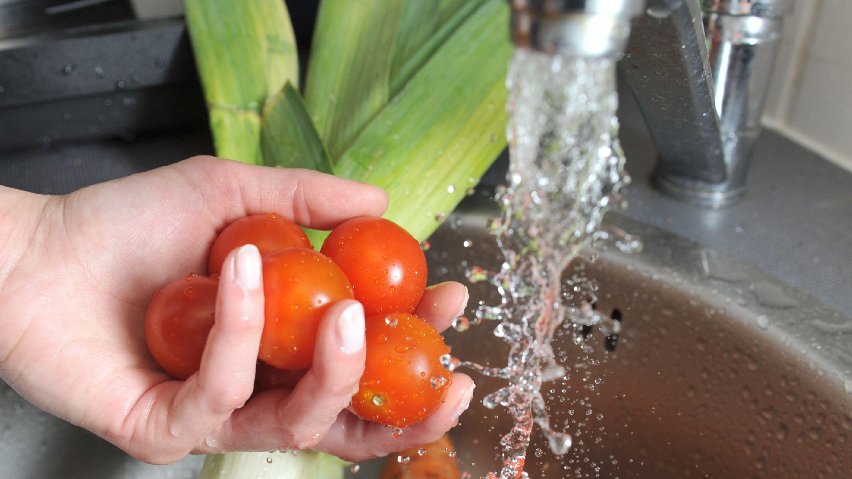 Gemüse wird unter einem Wasserhahn gewaschen