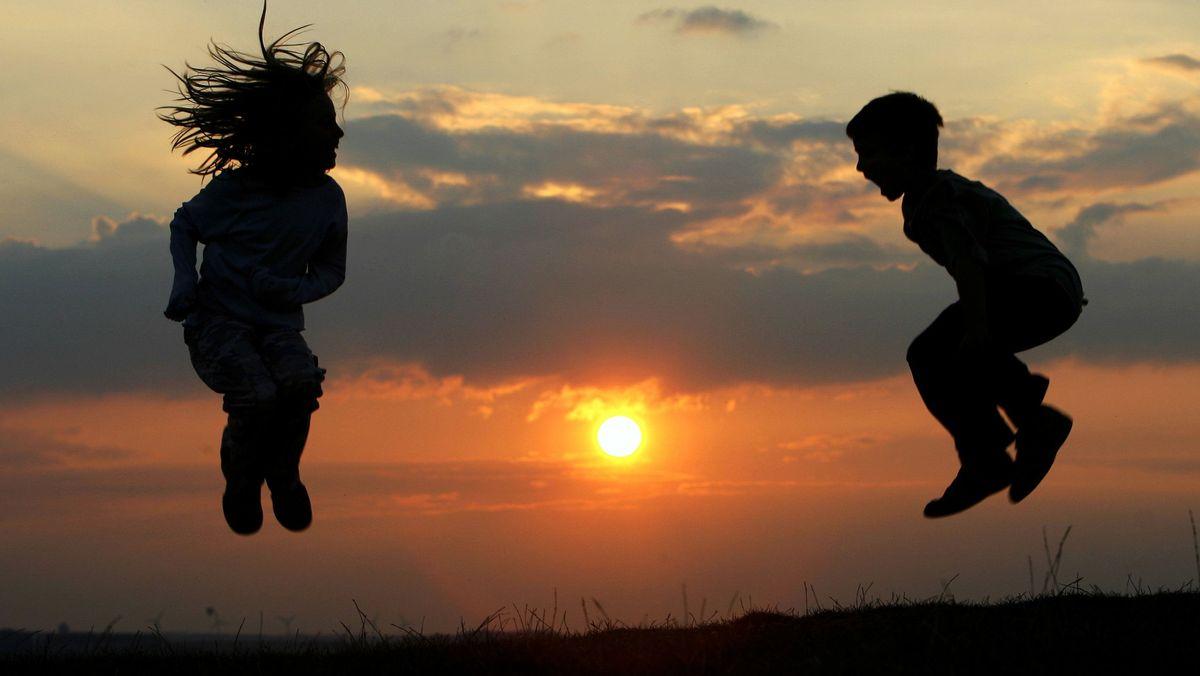 Zwei Kinder hüpfen vor einem Sonnenuntergang.