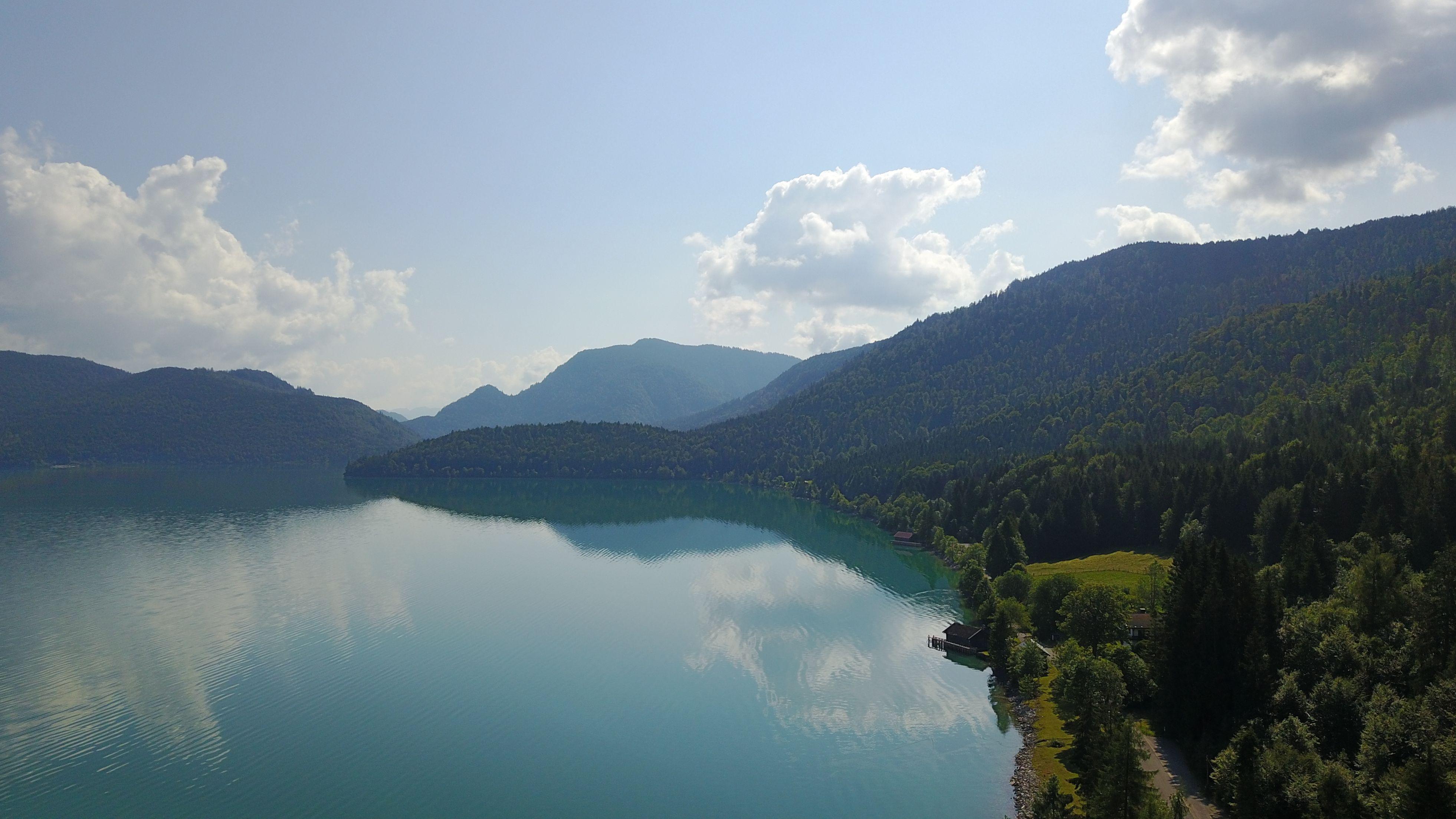 Blick von oben auf den Walchensee mit nahezu spiegelglatter Wasseroberfläche