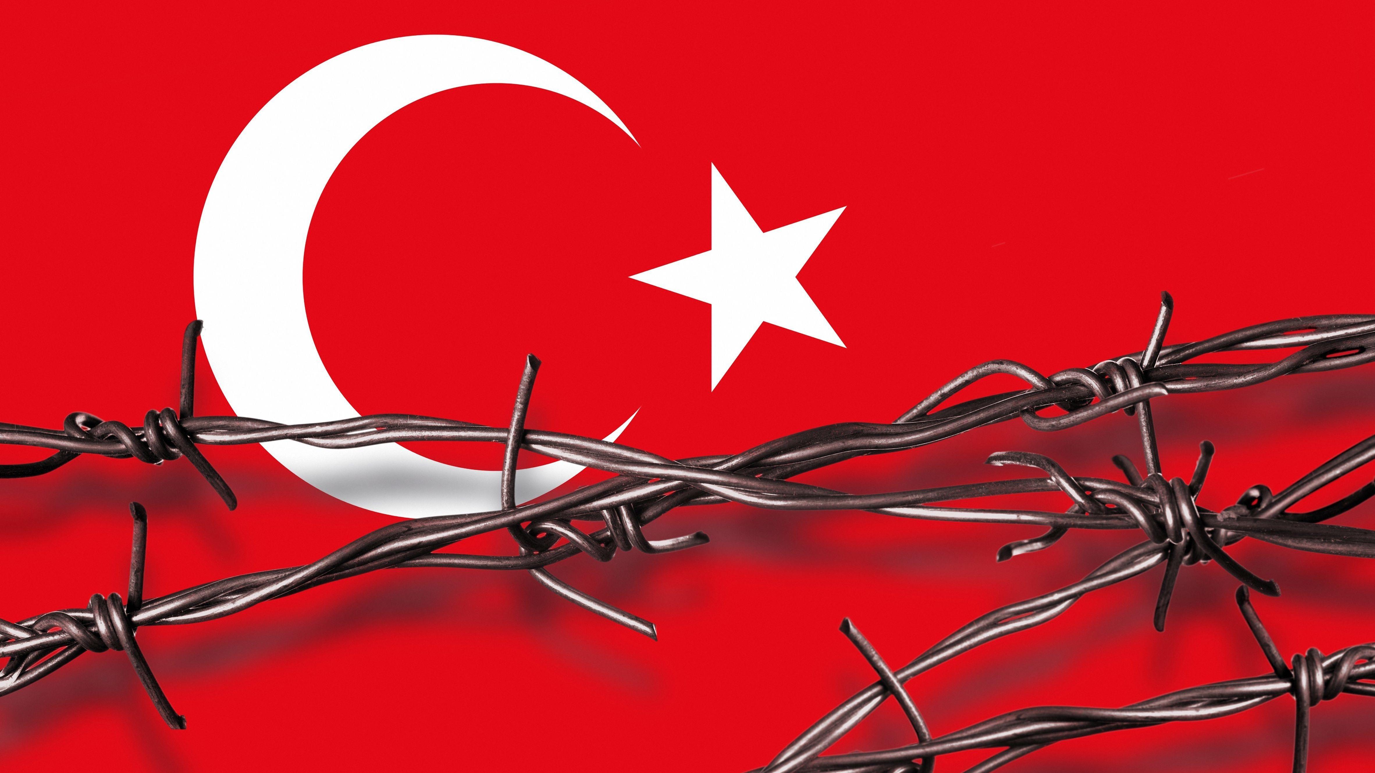 Stacheldraht mit Schatten vor einer türkischen Flagge