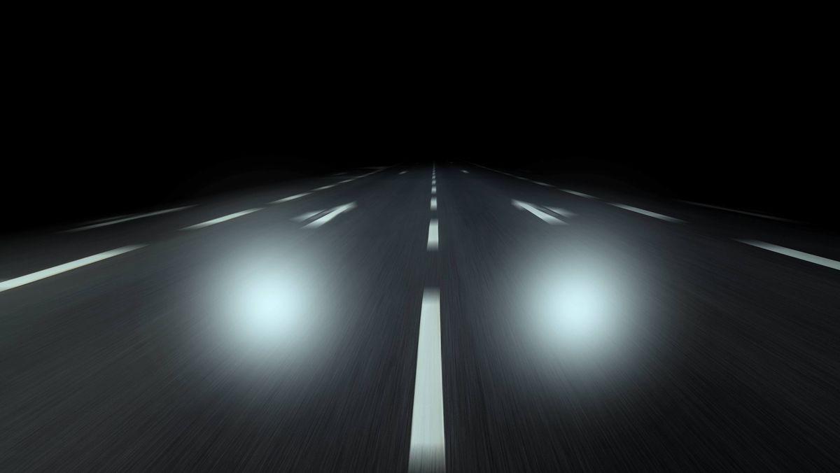 Lichtkegel eines Autos auf der dunklen Autobahn