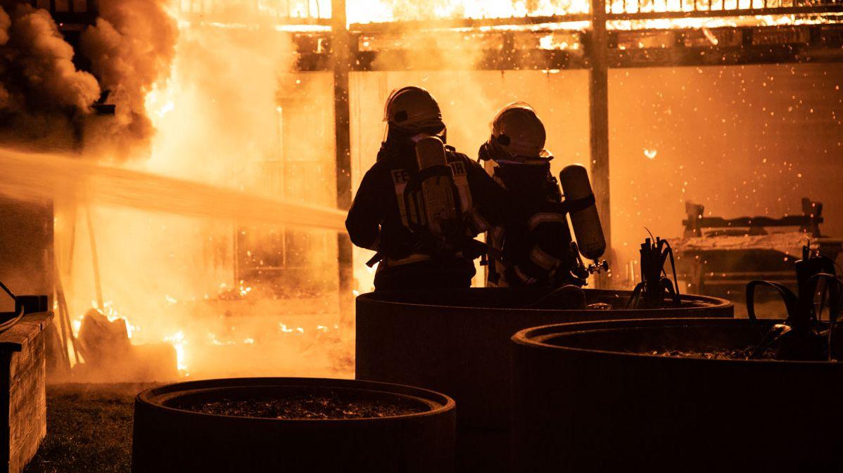 Das Haus im hellen Feuerschein, davor die Silhouette von zwei Feuerwehrmännern, die Löschwasser aus einem Schlauch ins Feuer spritzen