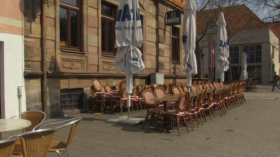 Abgesperrte Außenbestuhlung und geschlossene Sonnenschirme vor einem Café in Erlangen.