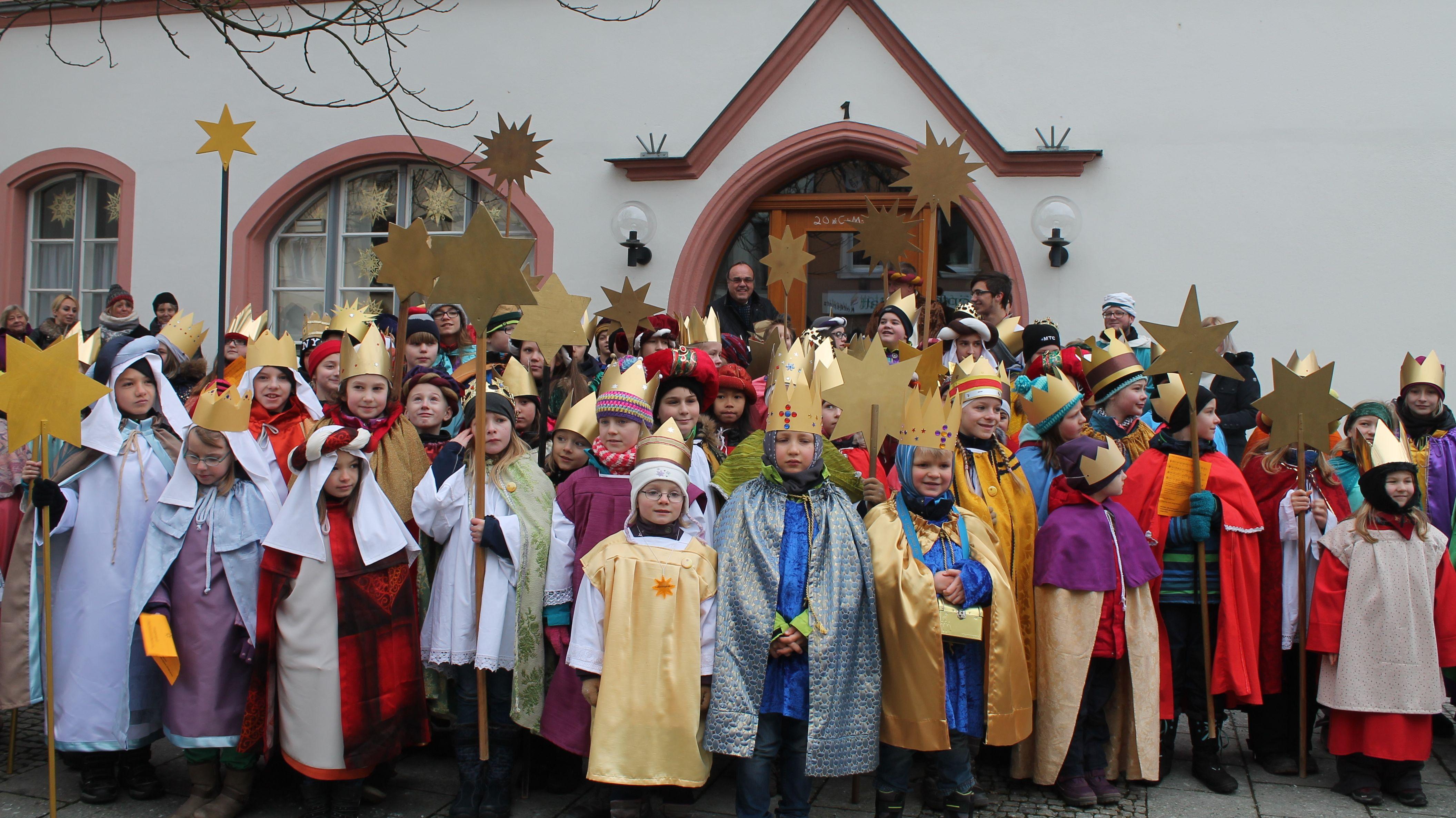 Mehr als 150 Sternsinger stehen in ihren prächtigen Gewändern vor dem Rathaus.