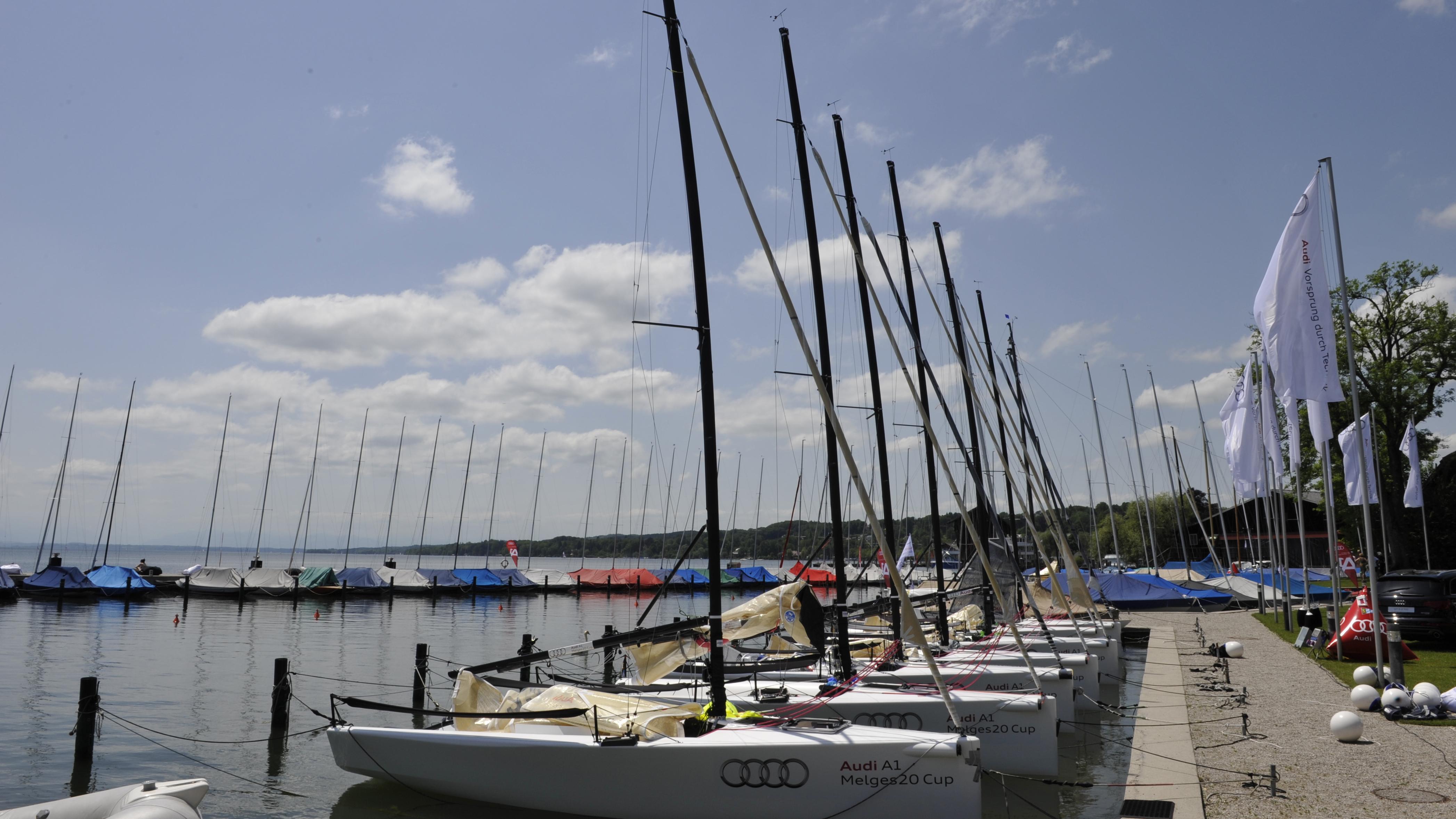"""Am Ufer des Starnberger Sees befinden sich mehrere Yachten, einige davon mit der Aufschrift """"Audi"""". Es ist schönes, sonniges Wetter. Auf dem Bild sind keine Menschen zu sehen."""