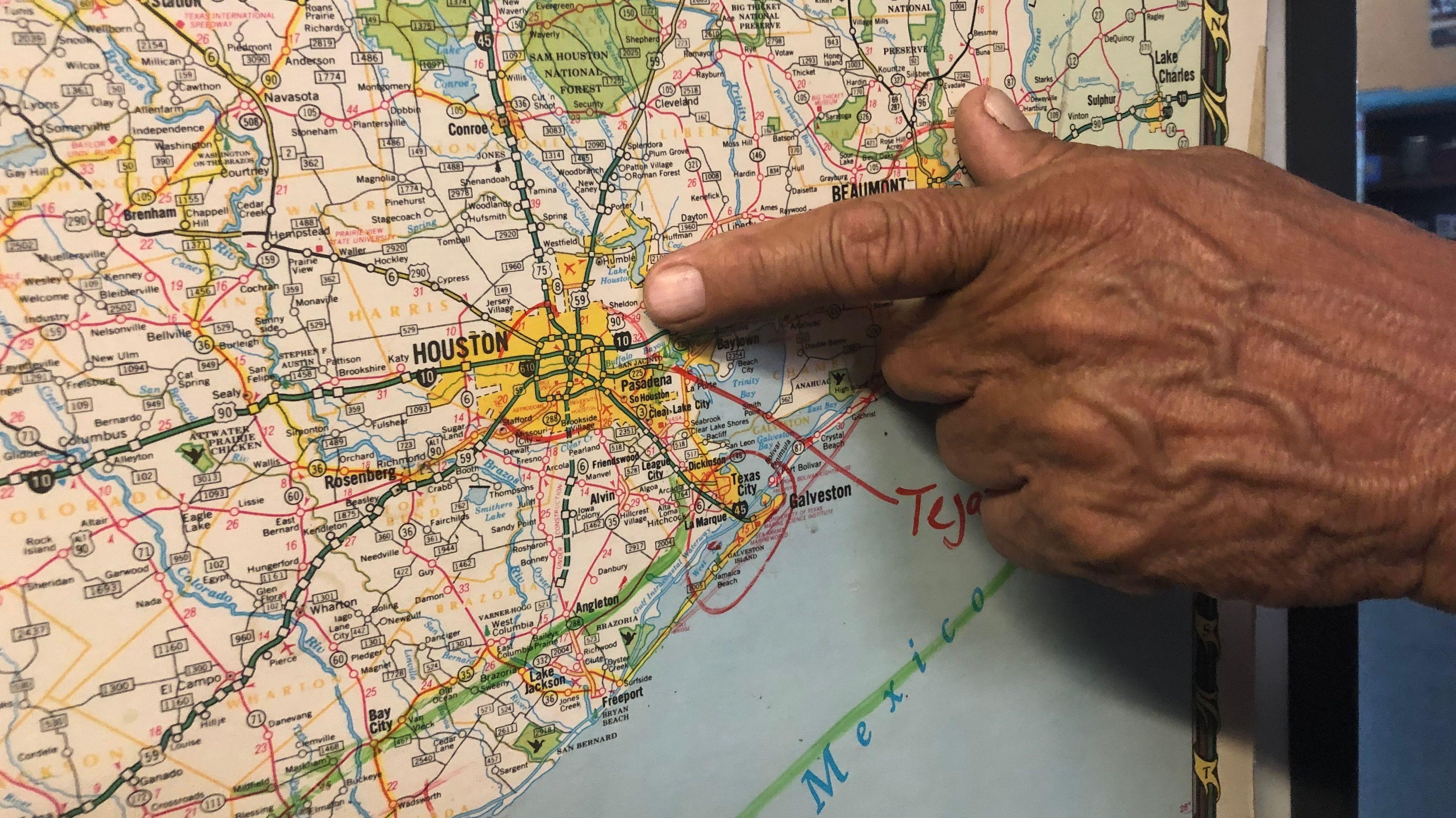 Juan Parras zeigt auf der Karte wo der Buffalo Bayou Fluss durch Houston fließt.