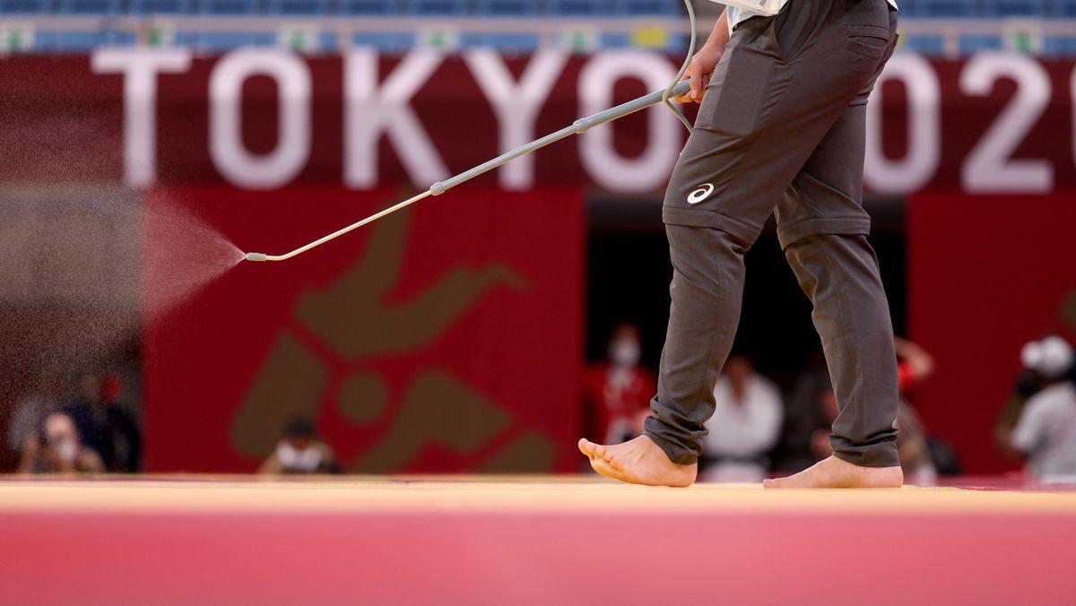 Judo: Olympia, Vorkampf, in der Kampfsporthalle Nippon Budokan. Mitarbeiter desinfizieren nach den Wettkämpfen den Boden.