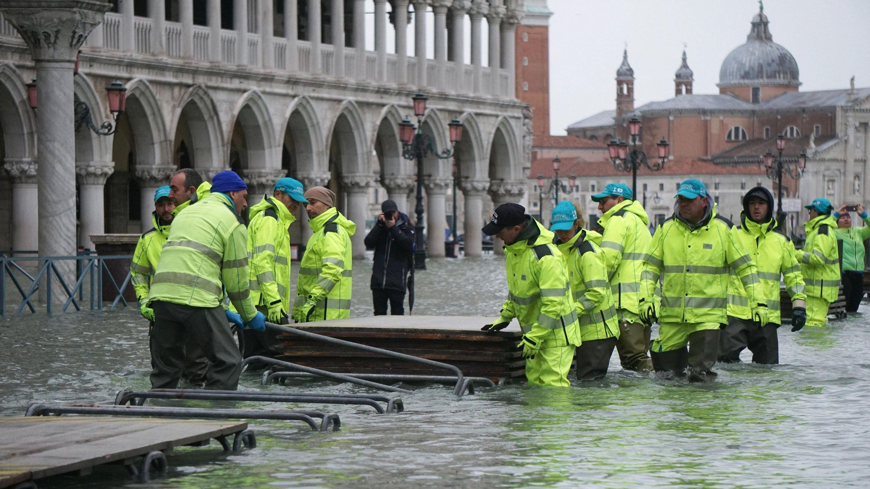 Helfer installieren auf dem überschwemmten Markusplatz einen Steg