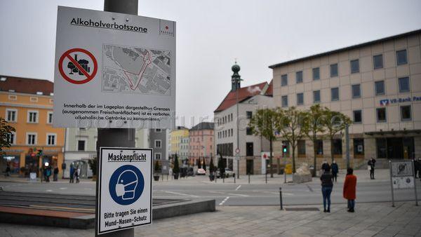 Schilder weisen am Ludwigsplatz auf die bestehende Alkoholverbotszone und die Maskenpflicht in Passau hin.