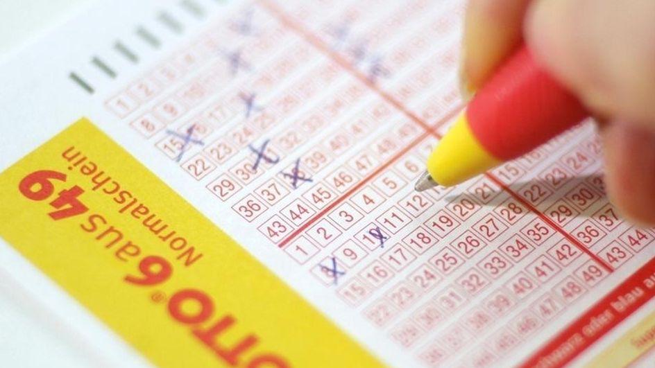 Auf eine gelb-roten Lottoschein kreuzt ein Spieler mit dem Kugelschreiber mehrere Zahlen an.