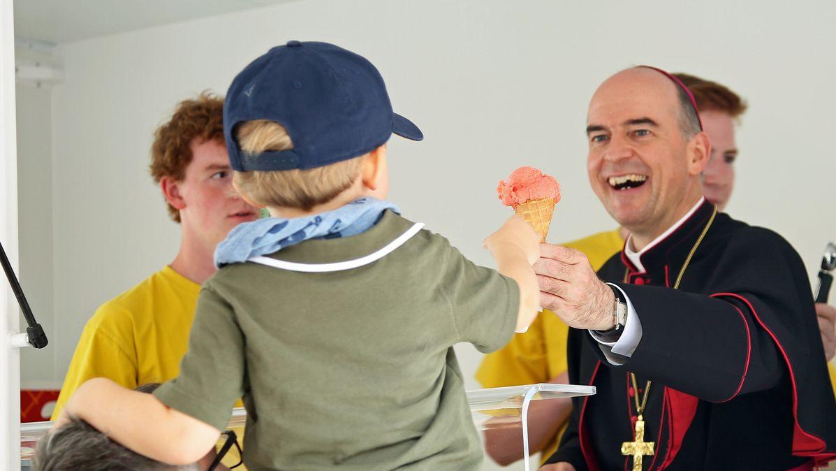 Bischof Franz Jung überreicht eine Eiskugel an ein Kind