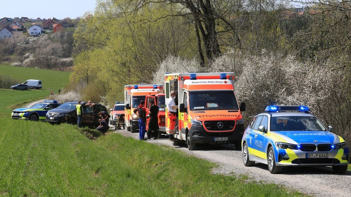 Einsatzfahrzeuge von Polizei und Rettungsdienst stehen auf einem Schotterweg.