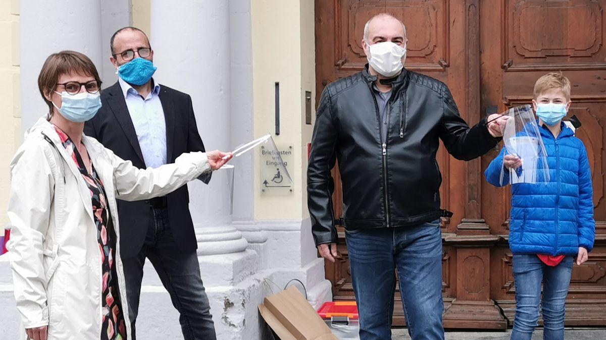 Die Kulmbacherin Helga Lormes und ihr Mann überreichen Gesichtsvisiere zum Schutz vor Corona an Vincenzo Coletta vor dem Kulmbacher Rathaus, alle Personen tragen einen Mund-Nasen-Schutz.