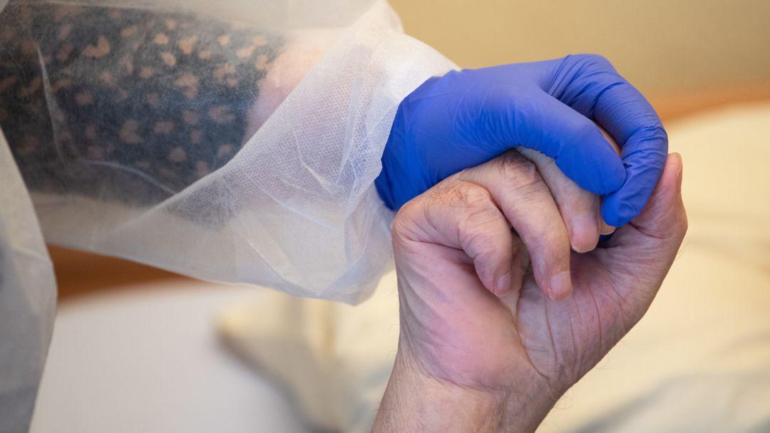 Symbolbild: Altenpflege in Corona-Zeiten. Eine Altenpflegerin in Schutzausrüstunghält die Hand eines Bewohners.