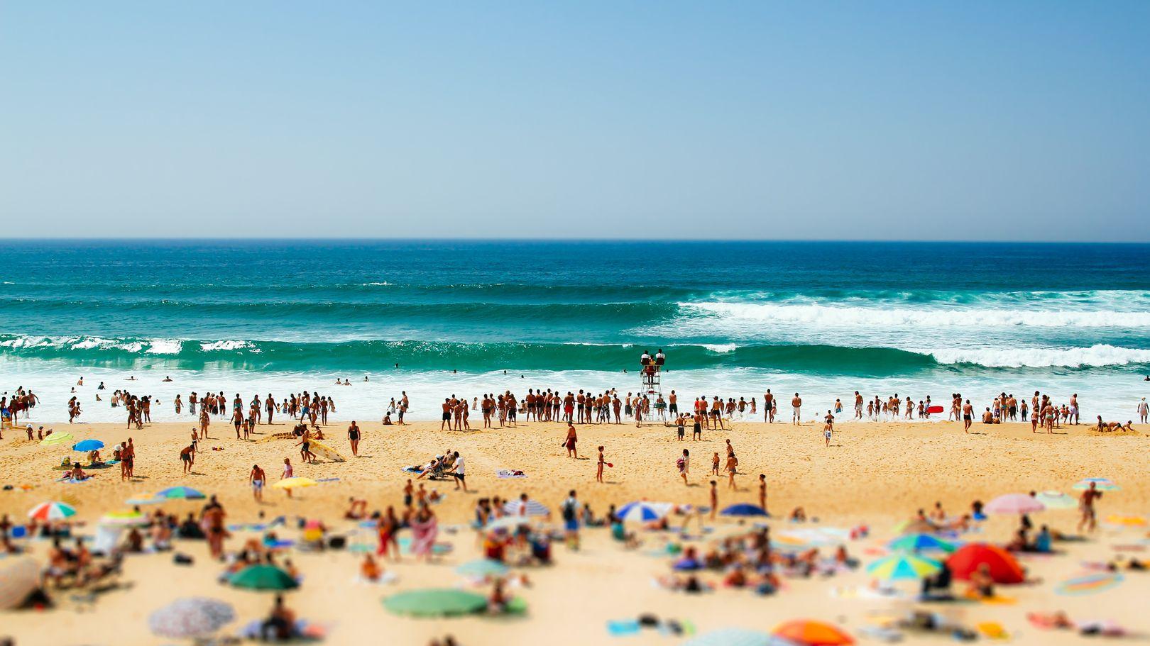 Menschen an einem Sandstrand.