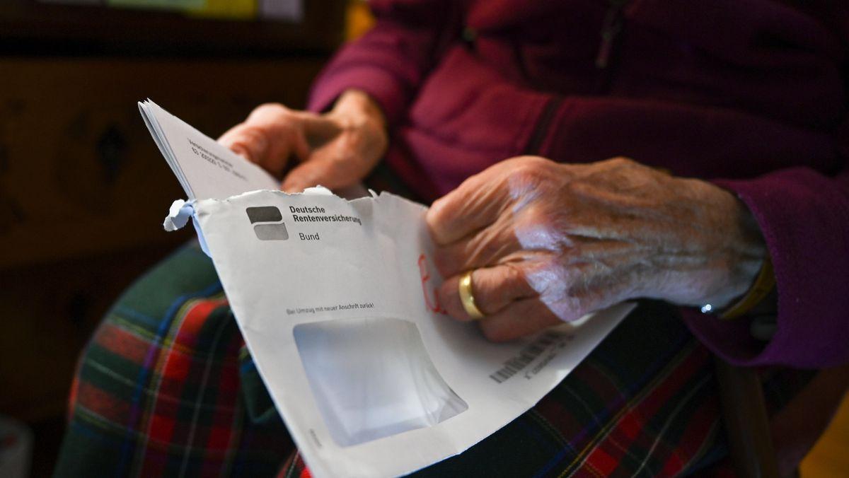 Seniorin öffnet Post mit Rentenbescheid
