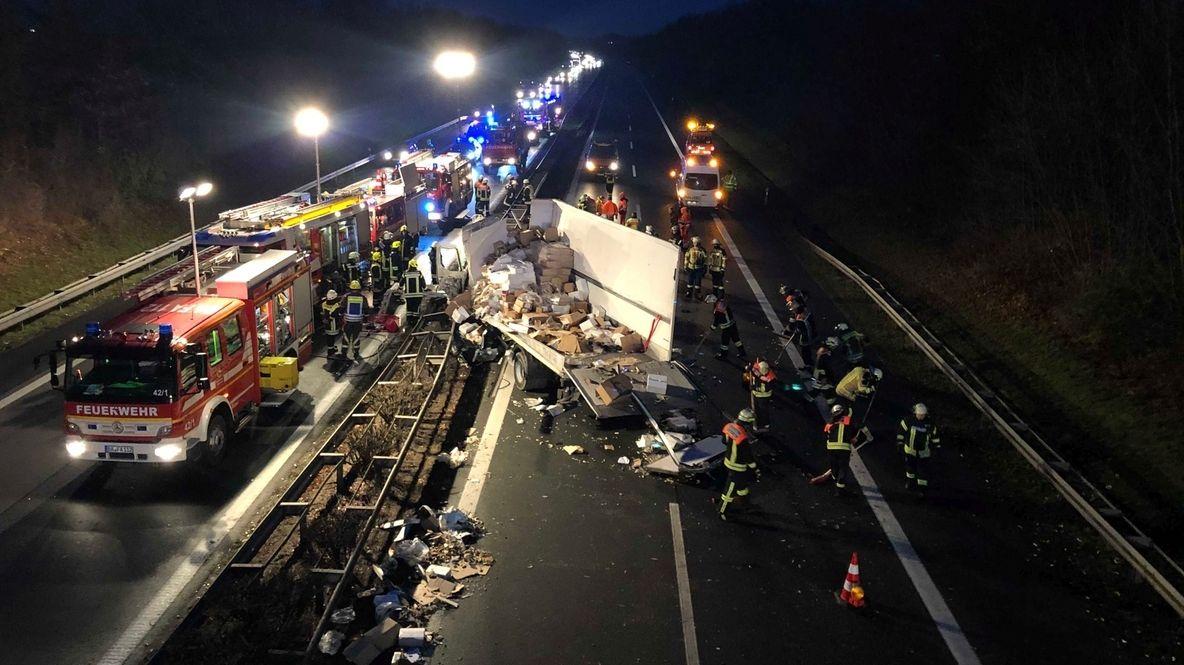 Ein Lastwagen liegt schwer beschädigt in einer Leitplanke, darum herum viele Fahrzeuge der Feuerwehr.