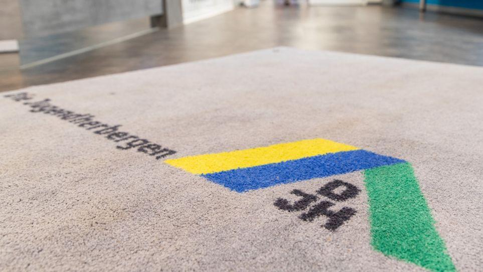 Ein Teppich am Eingang einer Jugendherberge mit Logo des Deutschen Jugendherbergswerks DJH