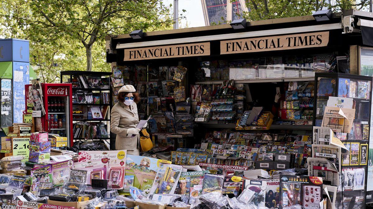 Frau mit Mundschutz an einem Zeitungskiosk