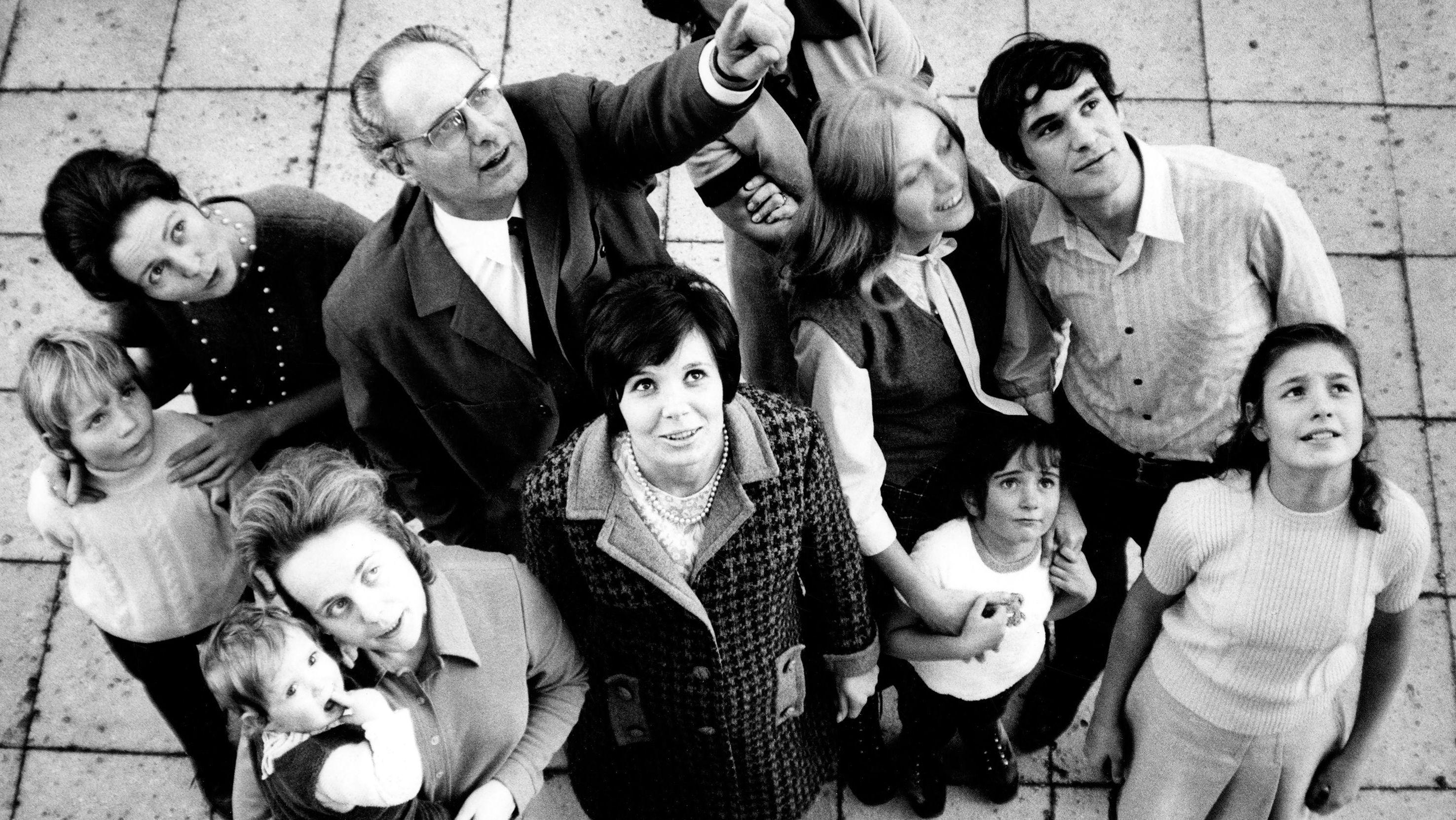 Gruppe von Menschen aus verschiedenen Generationen blickt nach oben.