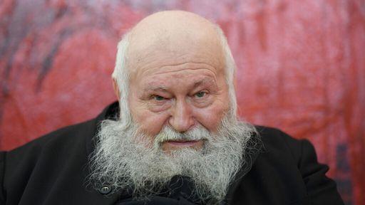 Der Künstler Hermann Nitsch mit langem weißem Bart schaut in die Kamera, im Hintergrund eine blutrote Wand.