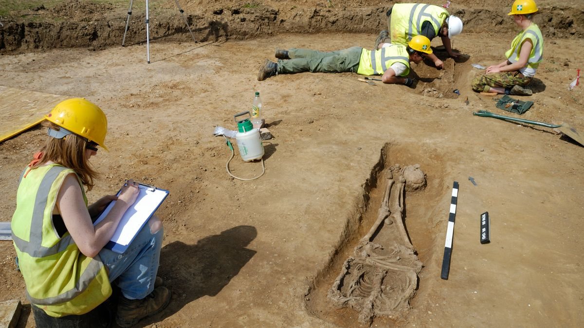 Frau mit gelbem Helm an einem Grab