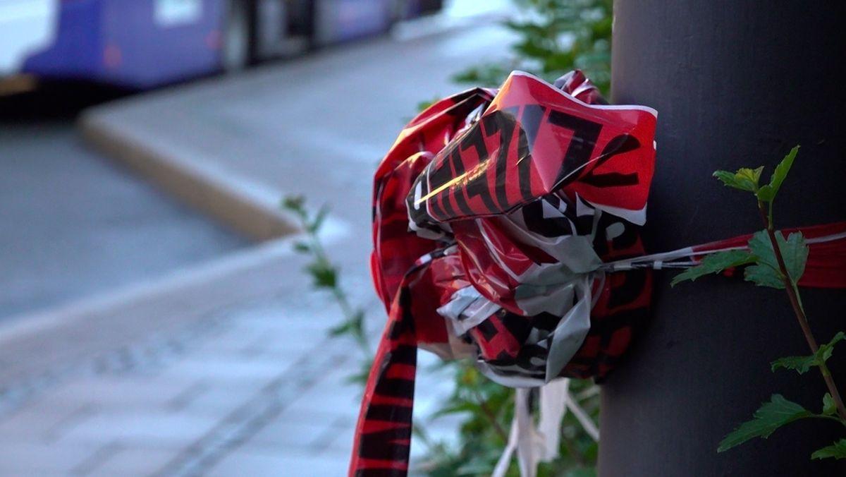 Ein zerknülltes rot-weißes Absperrband hängt an einem Laternenmast.