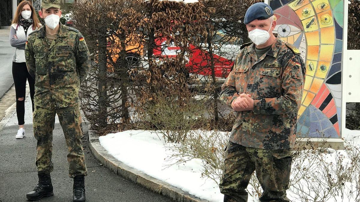 Generalarzt Bruno Most und ein weiterer Soldat in Uniform und mit Mund-Nasen-Schutz stehen vor einem Altenheim in Kulmbach, dahinter eine Frau mit langen Haaren.