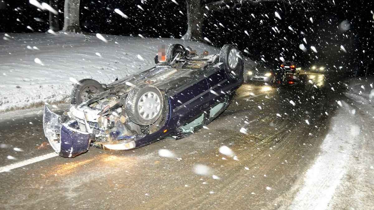 Schneeflocken und ein auf dem Dach liegender blauer PKW mitten auf einer Straße.