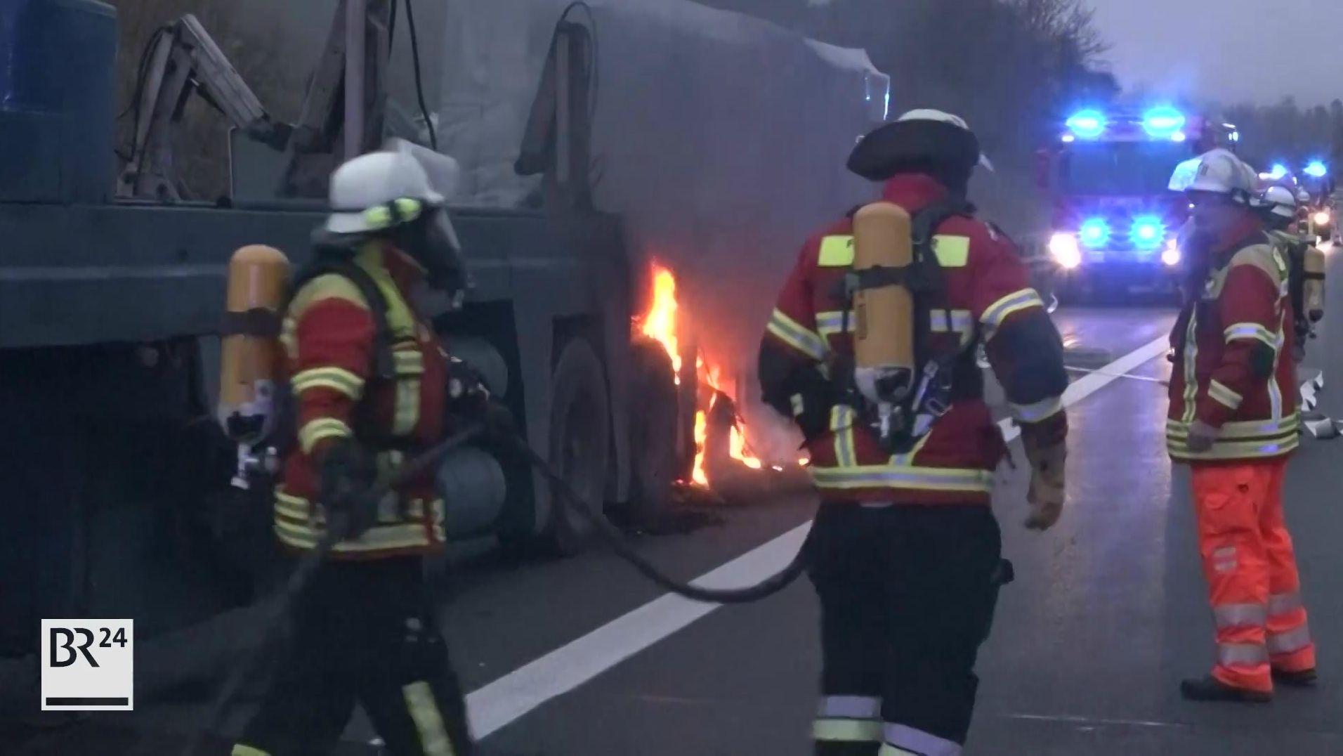 Ein lastwagenanhänger brennt, Feuerwehrleute löschen.