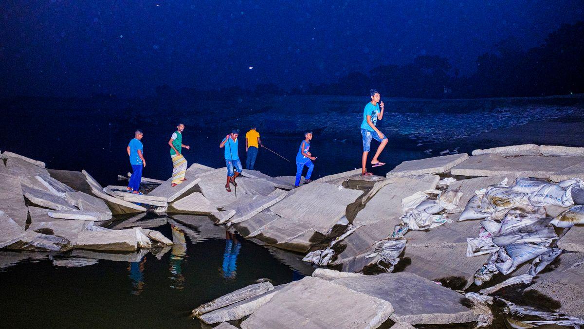 Sechs junge Männer in farbenfroher Kleidung klettern nachts auf Steinplatten am Meer herum