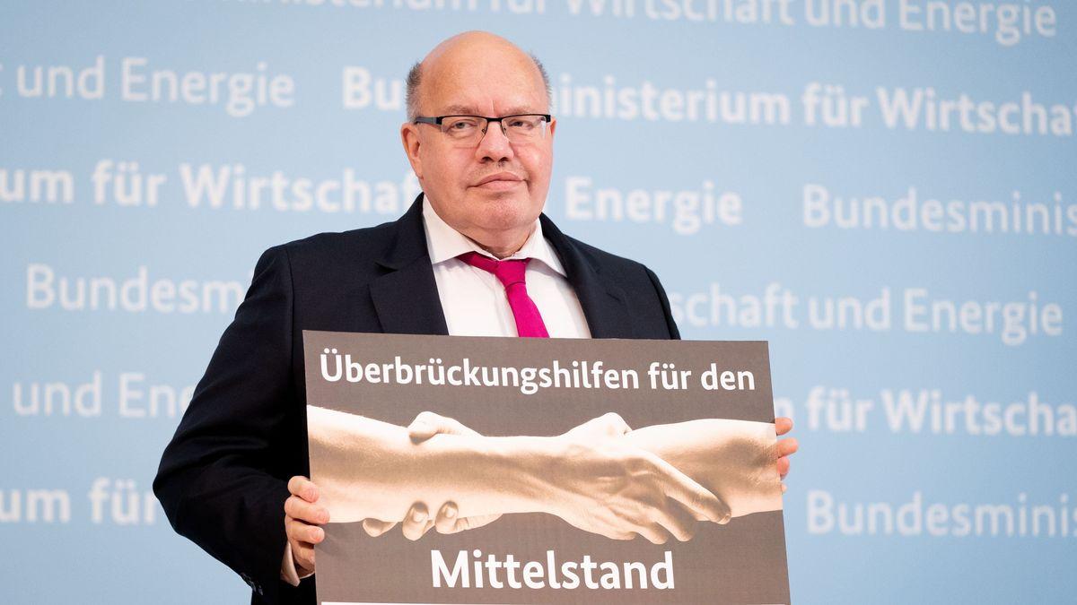 """Bundeswirtschaftsminister Peter Altmaier hält ein Plakat mit der Aufschrift """"Überbrückungshilfen für den Mittelstand"""" in den Händen."""