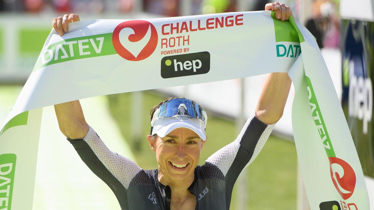 """Die Erstplatzierte Anne Haug aus Bayreuth jubelt im Ziel und hält ein Banner mit der Aufschrift """"Challenge Roth"""" in die Höhe."""