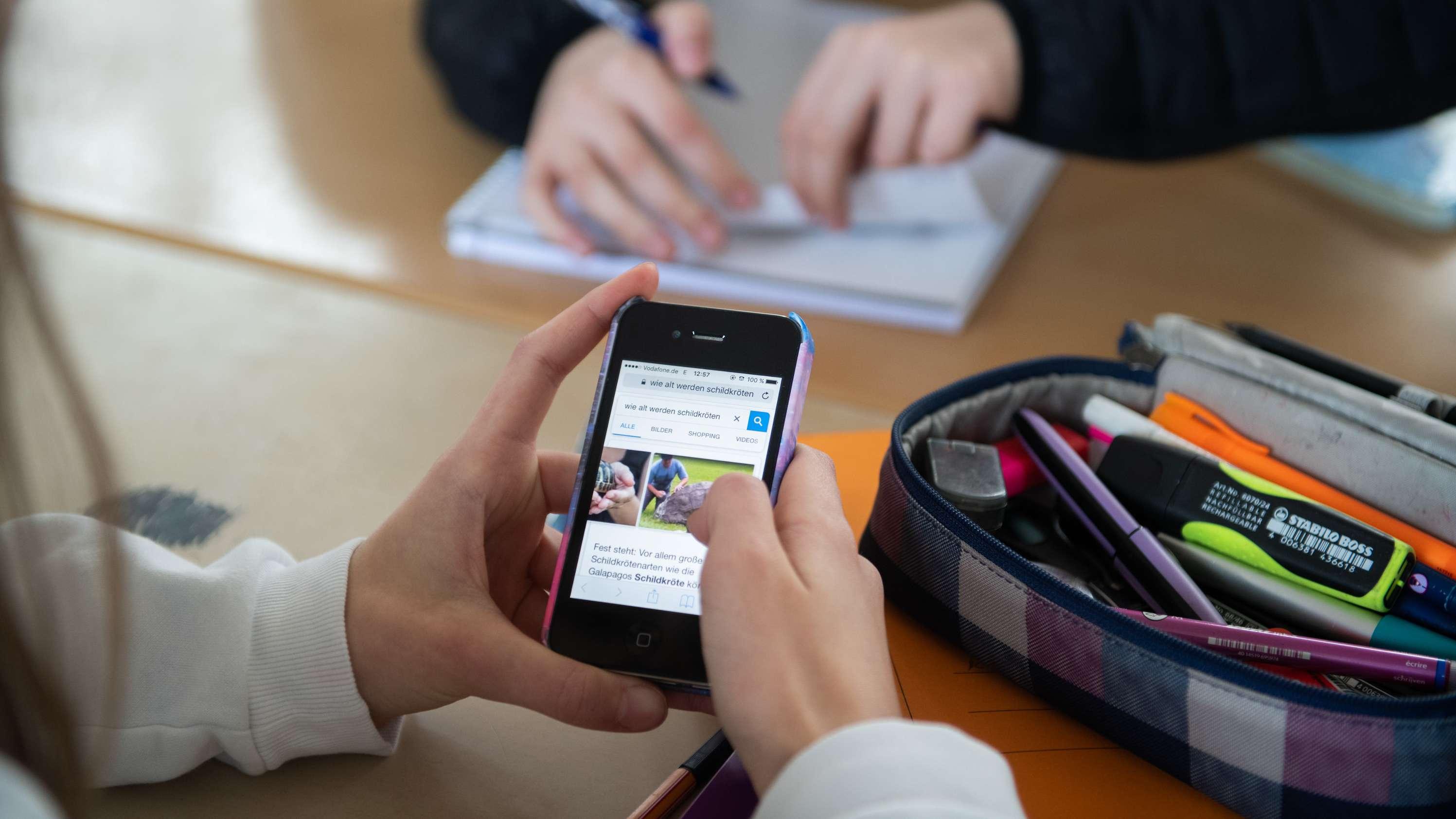Eine Schülerin nutzt ein Smartphone im Unterricht