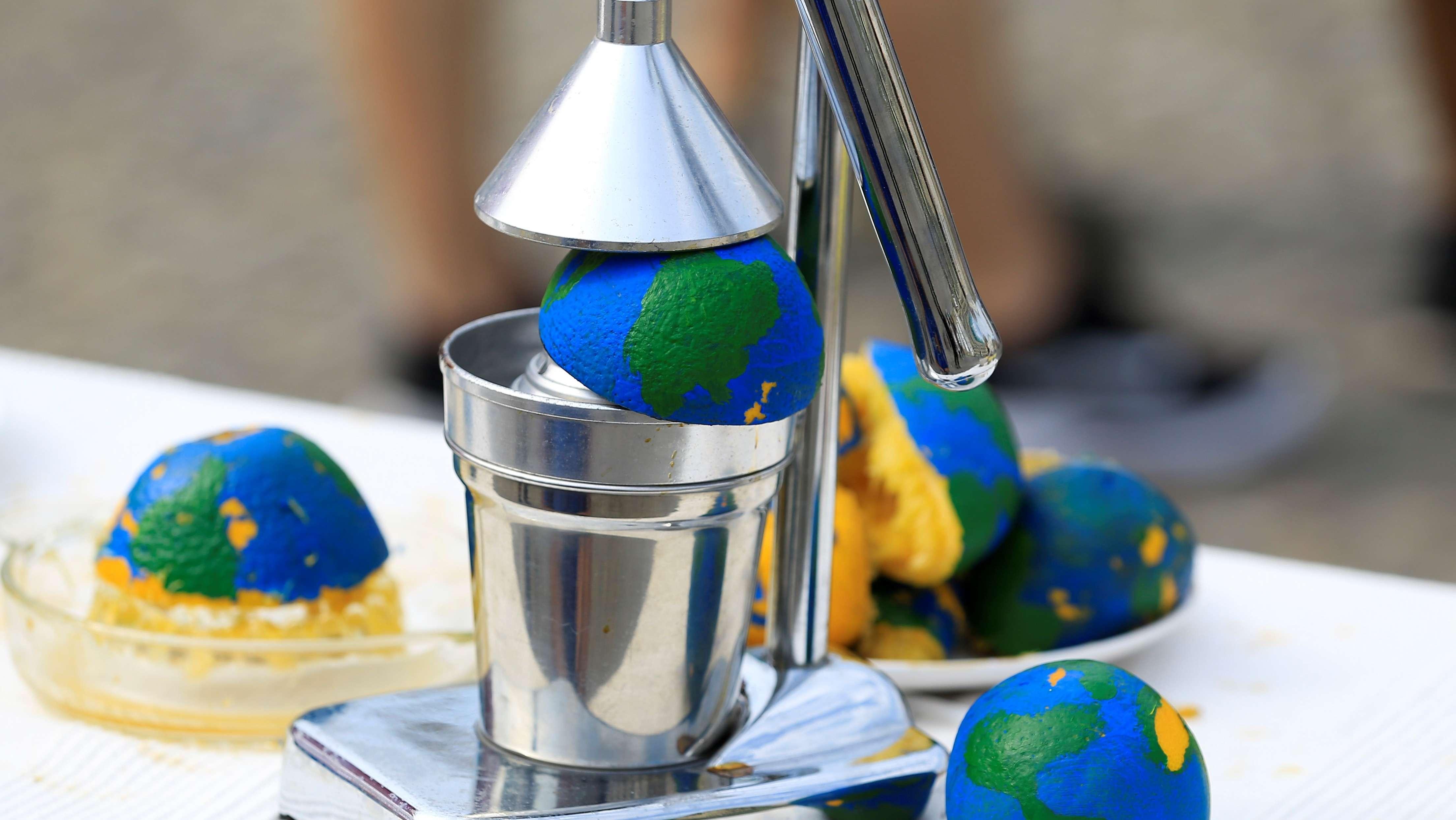 Symbolbild für den Earth Overshoot Day (Erdüberlastungstag, Tag der Ökoschulden) mit ausgepressten Orangen als Globus-Symbole