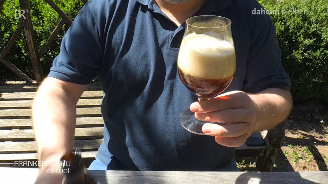 Ein Mann hält ein halbvolles Bierglas in der Hand.