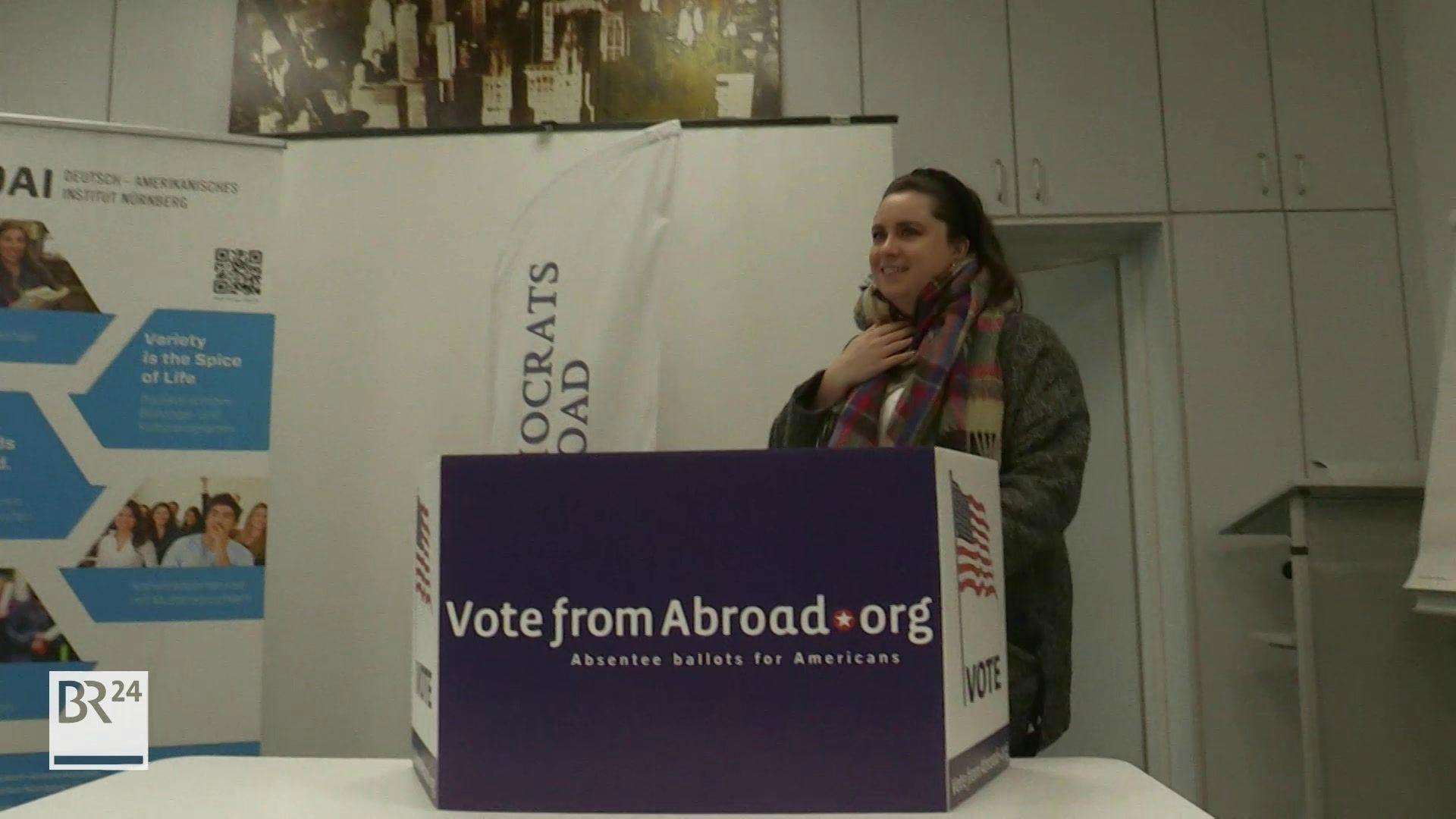 Frau setzt sich hinter eine Wahlkabine im Deutsch-Amerikanischen Institut in Nürnberg
