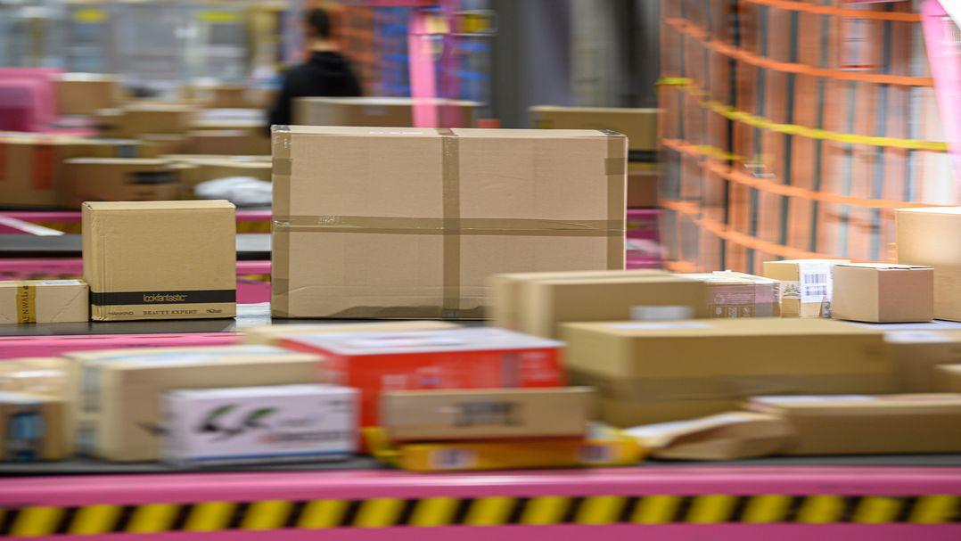Viele Pakete liegen in einem Paketzentrum auf einem Transportband